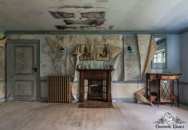 Rockstar Mansion England abandoned manor house blue bedroom with peeling wallpaper above fireplace
